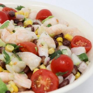chopped shrimp in a white bowl with sliced tomatoes and corn and beans
