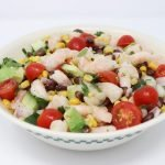 cilantro lime shrimp avocado salad in a white bowl with sliced tomatoes and corn and beans