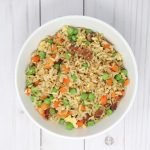 fried rice with bacon and vegetables in a white bowl