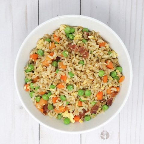 fried rice with bacon and vegetables in a white bowl top view