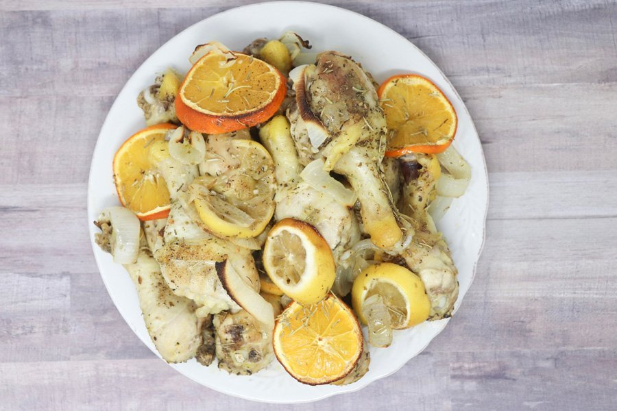 herb and citrus oven roasted chicken drumsticks with onions and citrus on top