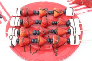 fruit kabob strawberries, blueberries, and marshmallows on a skewer drizzled in chocolate