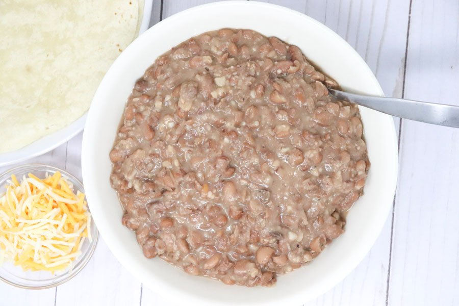 refried pinto beans in a white bowl with cheese and a tortilla
