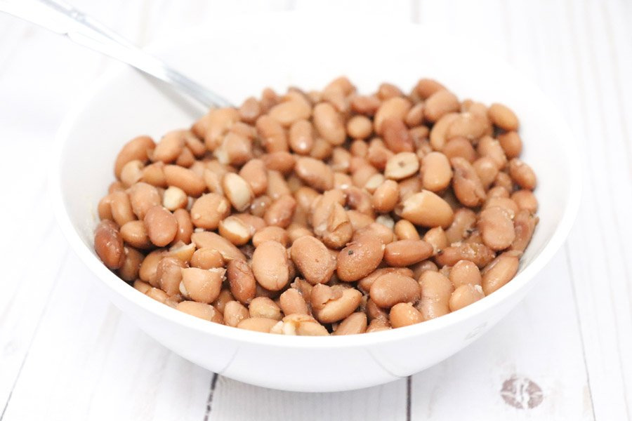 whole cooked pinto beans in a white bowl