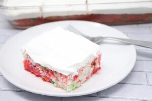skinny funfetti poke cake with whipped topping on a white plate