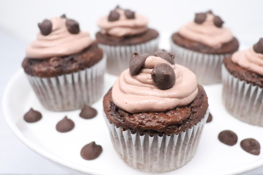 chocolate cupcake with chocolate whipped frosting on a white stand