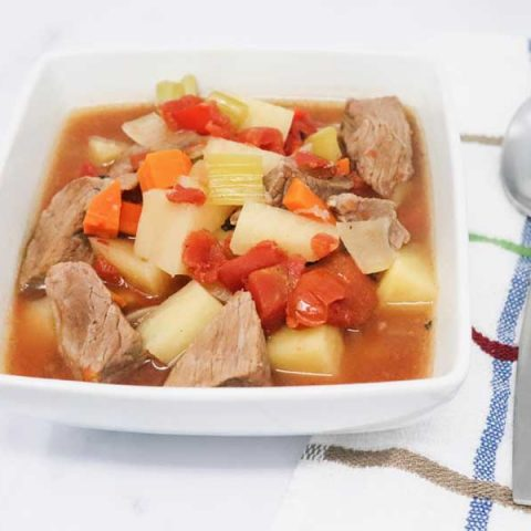 beef stew in a white square bowl sitting next to a spoon on a towel