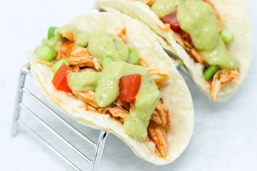two salsa chicken tacos drizzled with avocado sauce in a taco stand
