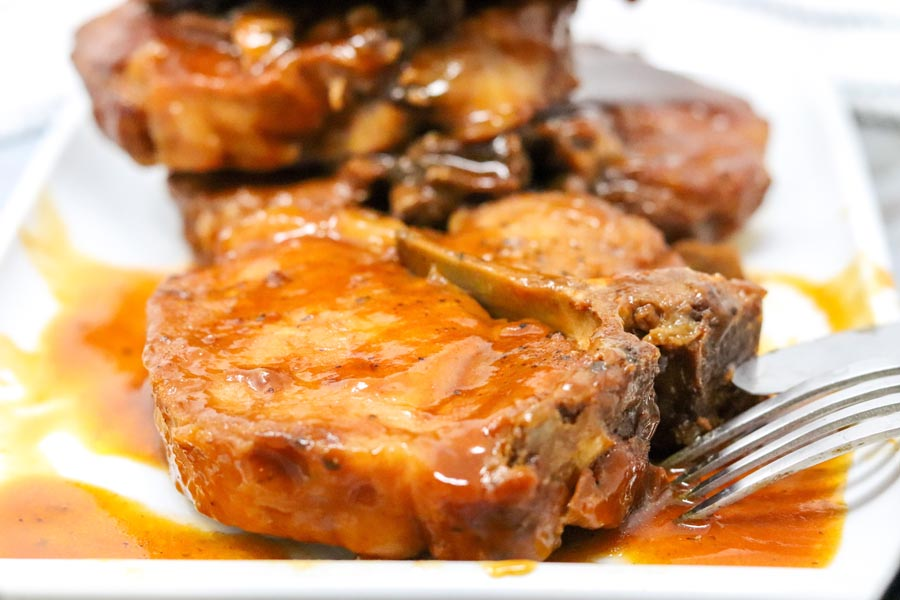 saucy pork chops on a white plate with one in focus