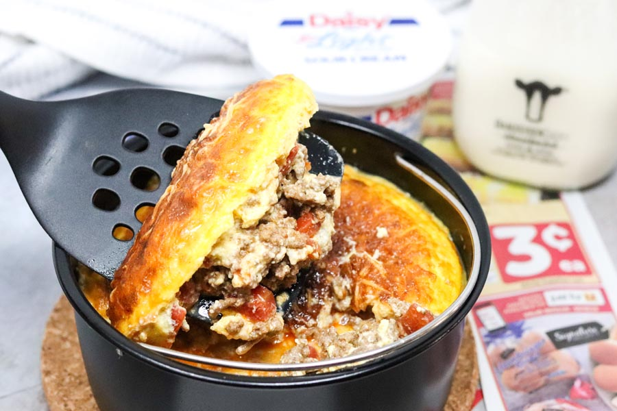 pan of taco casserole with a spatula scooping the casserole out of the dish with milk and sour cream in the background
