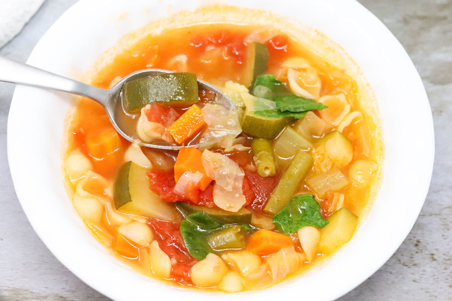 bowl of vegetable soup with a spoon scooping some of the soup