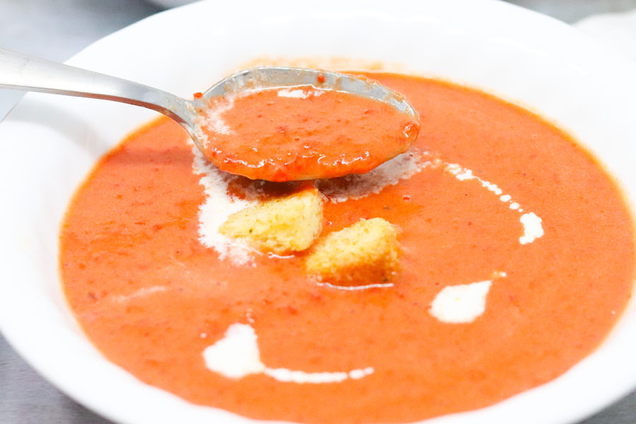 roasted red pepper and tomato soup in a white bowl being scooped with a spoon
