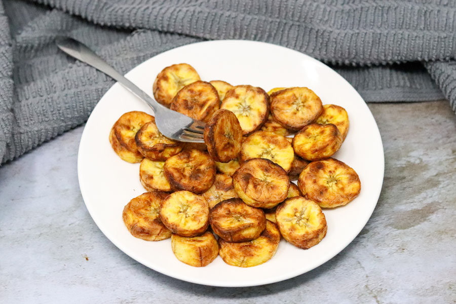 cooked sweet plantain on a white plate with a fork