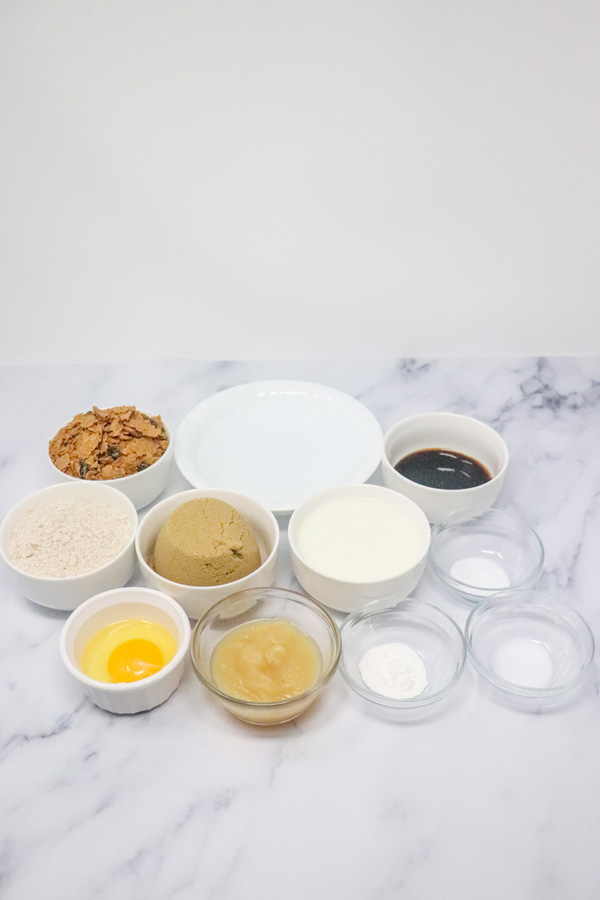 honey bran muffin ingredients set out on a marble background